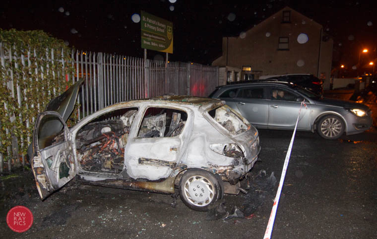 Police guard the scene - the remains of a burnt out car  at the rear of St Paticks Primary School, Newry. Photograph: NewRayPics