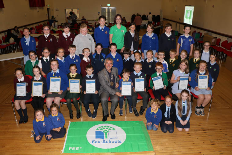 Cathy Gorman Eco Schools Officer, Keep Northern Ireland Beautiful and Cllr Mark Murnin, Chairperson Newry, Mourne and Down District Council with the Eco Councils from ten primary schools, including St Peter's PS Cloughreagh, St. Patrick's PS Hilltown, St. Mary's PS Mullaghbawn, Castlewellan PS who each received their 1st Green Flag, Windsor Hill PS Newry wo received their 2nd Flag, St Laurence O'Toole PS Belleeks who received their 3rd Flag, St. Bronagh's PS Rostrevor with their 3rd Flag, St. Malachy's PS Carnagat with their 4th Flag, Cumran PS Clough Downpatrick with their 8th Flag and Downpatrick Nursery School with their 10th Flag.