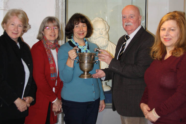 Presentation of the silver cup to Newry and Mourne Museum.  L-R: In front of bust of James MacGeorge: Sue Coles, Sheila Pocock, Kate Pocock, Councillor Charlie Casey and Noreen Cunningham, Museum Curator.