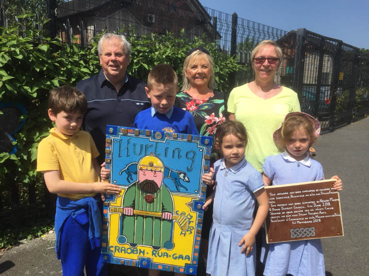 Bronnadh- A Presentation of Children's Artwork  at Bunscoil an Iúir . Pictured are young Craobh Rua players , Lughán, Tommy , Éabha agus Mairéad along with staff from the Bunscoil and Labhrás Bradley who accepted the gift on behalf of Craobh Rua Camlocha