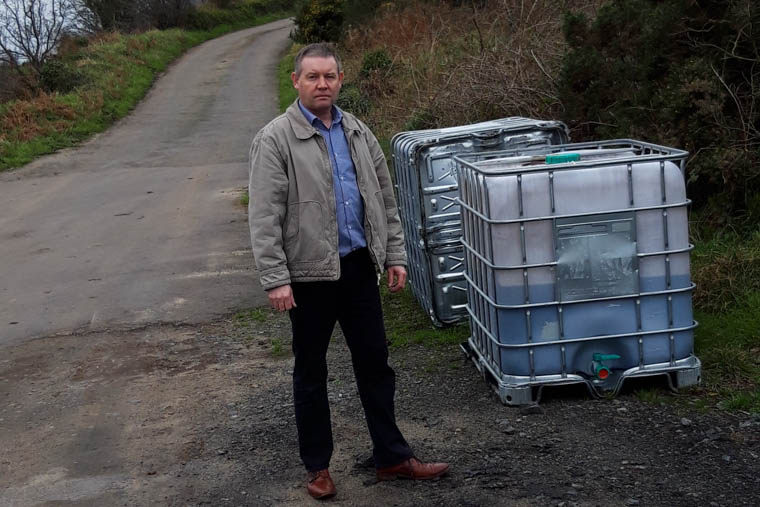 Cllr Mickey Larkin with two of the diesel tanks dumped over Christmas and New Year.
