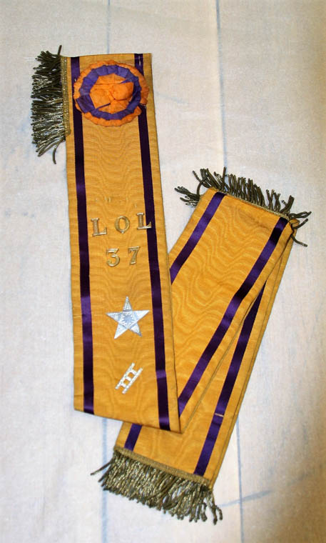 A sash from the private lodge of Altnaveigh LOL 37 which is a lodge within Newry District LOL No 9.  They are worn by the Orange Order during parades and demonstrations.  In more recent decades, sashes have been replaced by collarettes. Newry and Mourne Museum Collection