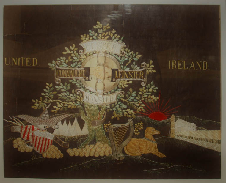 A textile panel believed to have been produced in America in the early 1900s.  The embroidered panels are filled with Irish Nationalist, and patriotic American, symbols. Newry and Mourne Museum Collection