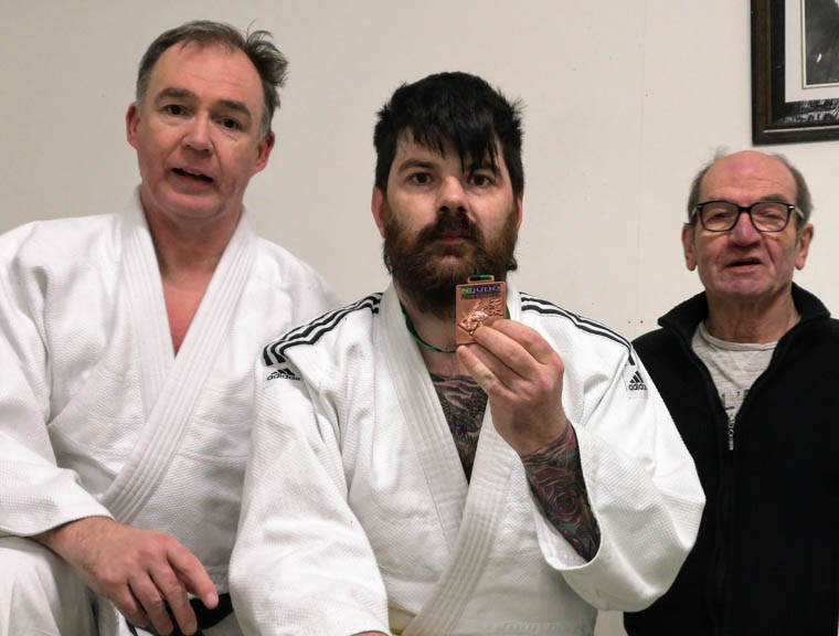 Shinken Shobu Ryu Judo Club member John McKinney with his bronze medal from the Inaugural Adaptive Judo Open competition. Also included are Dermot McCaul, left and Eddie Donnan, right.