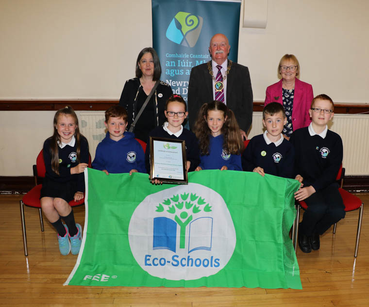 St. Oliver Plunkett's Primary School Forkhill received their First Green Flag at the Annual Eco-School Green Flag Ceremony in Warrenpoint Town Hall. Front from left: School Eco Council Holly Cunningham, Finn McConnon, Ella Matthews, Lillie Farmer, Declan Conlon and Justin Bird. Back from left: School Eco Co-ordinator Patricia McKenna, Chairperson Newry, Mourne and Down District Council, Councillor Charlie Casey and Dorothy Corkin Eco-Schools Assessor.