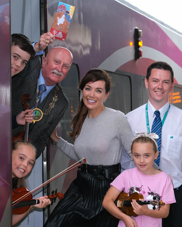 All aboard the Iúr Cinn Fleadh Trad Train! - Cllr Charlie Casey, Chairperson, Newry, Mourne and Down Council is looking forward to welcoming musicians and visitors from Dublin to Newry on Saturday 7 September for Iúr Cinn Fleadh, the city's annual festival of trad and folk music.  Also included in photograph are Niamh, Aoife and Oisin Cunningham from Newry School of Traditional Music. Ross Earley, Events Supervisor, Translink and Claire Byrne, Iúr Cinn Fleadh.  You can have a day out with a difference. Take the Enterprise (Coach G) from Dublin Connolly to Newry, where Irish Traditional Musicians will entertain you all the way. Spend the day at Iúr Cinn Fleadh checking out the multitude of events, then that evening on your return enjoy the session on way back to Dublin. Book your ticket via normal booking system at www.translink.co.uk or www.irishrail.ie for best deals or just buy on the day (Note: You can choose to travel just one of the legs of the journey and depart/return at another time/ date or travel both)  Saturday 7 September 2019 | Depart Dublin Connolly 11.20 Arrive Newry 12.36. Depart Newry Train Station 19.02 Arrive Dublin Connolly 20.17 (Free bus to/from Newry Train Station - Departure from Newry Buscentre 18.35) Photograph: Columba O'Hare/ Newry.ie