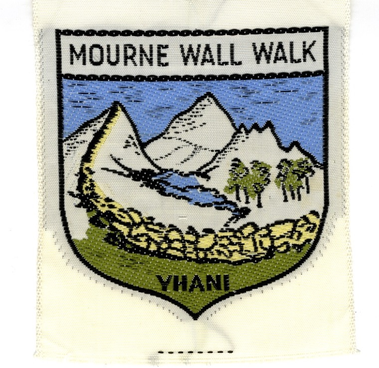 Badge worn by participants in the Mourne Wall Walk which was established by the Youth Hostel Association of Northern Ireland in 1956. Walkers walked the entire length of the Wall and it increased in popularity over the years until it was halted in 1984 due to damage to the environment. Only small groups are now allowed to walk the route. Newry and Mourne Museum Collection