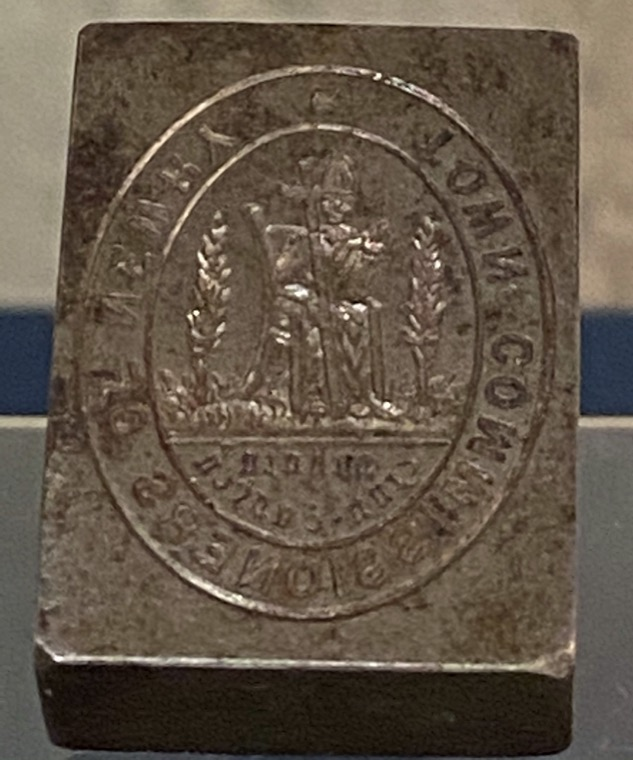 The 19th- century seal of the Newry Town Commissioners featuring the mitred abbot flanked by the yew trees traditionally associated with St. Patrick.  Newry and Mourne Museum Collection