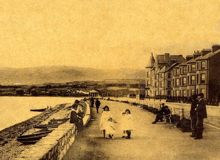 The promenade at Warrenpoint, pictured c.1900, with a bandstand and impressive seafront buildings, had been developed under the patronage of the Hall family in the 19th century. This was a focal point for people to enjoy their leisure.   Newry and Mourne Museum Collection