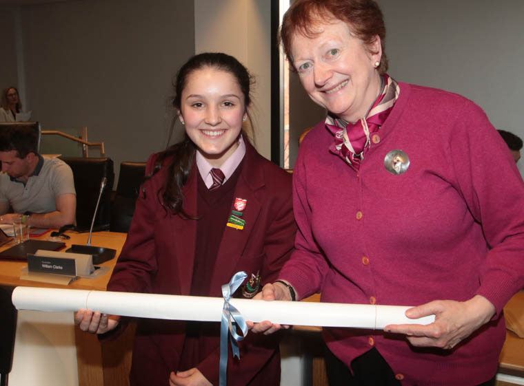 Molly McCartan from St Mary's High School receives a copy of the UN charter from UNA NI representative Carol Conlin.