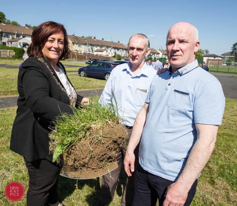 Chairperson of Newry, Mourne & Down District Council, Gillian Fitzpatrick  cuts the first sod  under the eye of  Drumalane Quayside Close Community Association Chairman, Gerard Hutchinson  and Secretary, Gerry Coye.