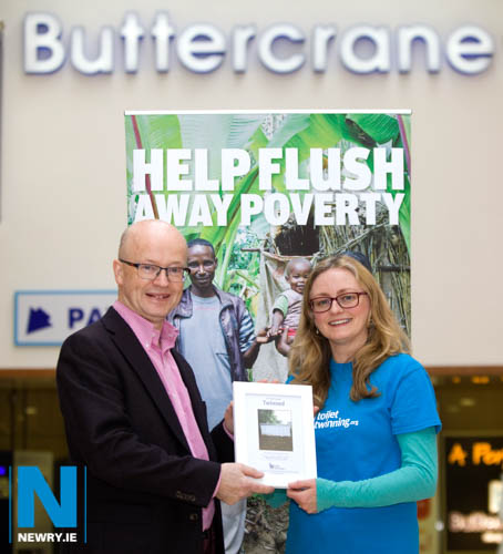 Buttercrane Manager Peter Murray with Susan Bennett, Toilet Twinning Fundraising Manager Northern Ireland checking out a photograph of the latrine block in Africa which is twinned with Buttercrane Shopping Centre toilets.
